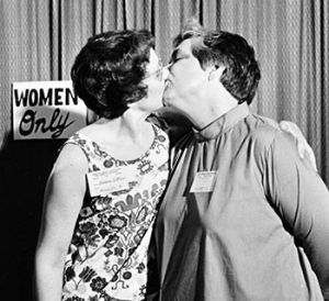 Barbara Gittings and author Alma Routsong kiss each other at the Task Force on Gay Liberation's Hug-a-Homosexual booth in the exhibit hall at ALA's 1971 Annual Conference in Dallas.Photo: ALA Archives