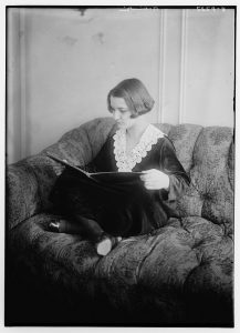 woman reading while seated on couch