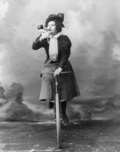 [Madge Lessing, full length, on bicycle, facing left; holding musical horn to lips]. Photograph copyrighted by E. Chickering, c1898. Library of Congress Print s& Photographs Division. //www.loc.gov/resource/cph.3b10346/