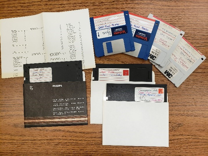 "four 3.5"" floppy disks, three 5.25"" floppy disks, and a piece of paper with file listing."