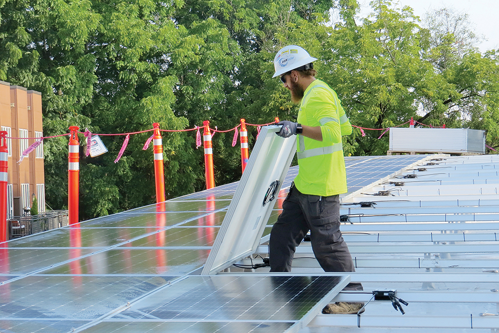A worker installs solar panels on the roof of Ledding Library in Milwaukie, Oregon. Photo: Katie Newell/Ledding Library in Milwaukie, Oregon