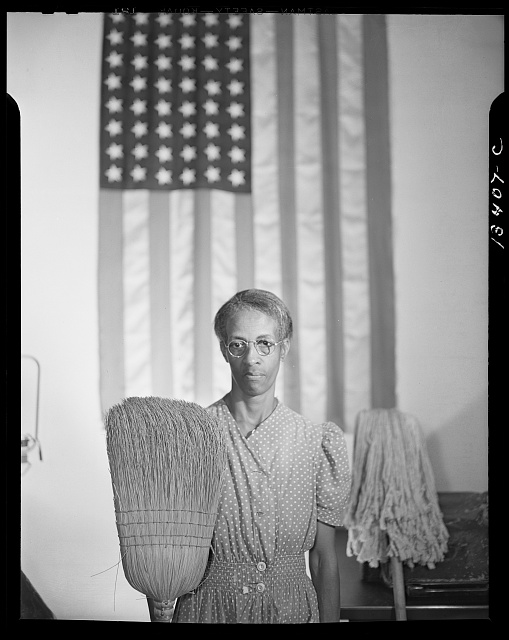 Photograph by Gordon Parks of Ella Watson with mop and broom in front of American flag