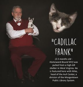 Librarian in red vest poses with kitten named Cadillac Frank