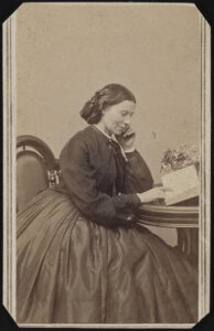 Sepia-toned 1865 photograph of Clara Barton. She is seated at a desk, reading, smiling and resting her head chin on her left hand.