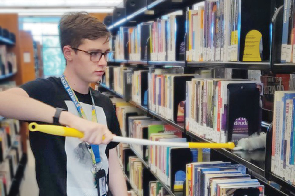 Jack Miller dusts shelves at the main location of Gail Borden Public Library District in Elgin, Illinois, pre-pandemic. Photo: Gail Borden Public Library District in Elgin, Illinois