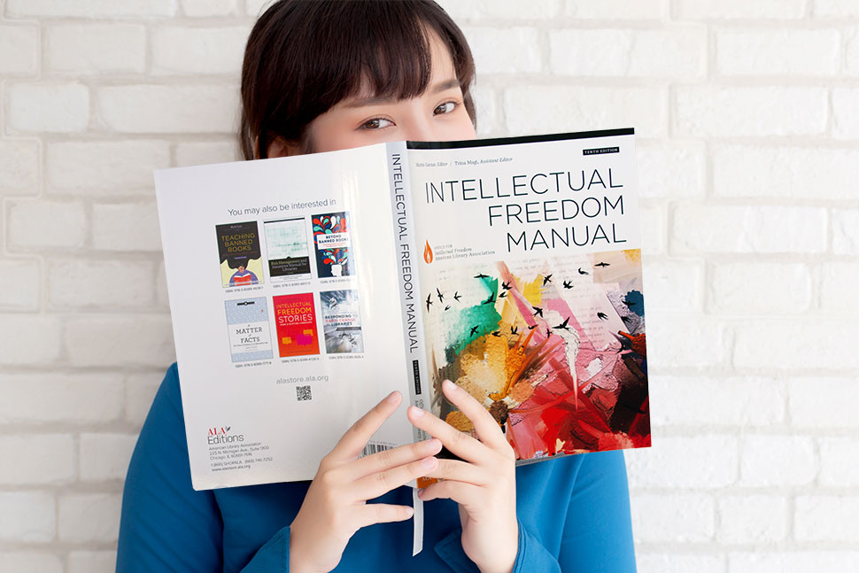 Young woman in blue shirt reads the 10th edition of ALA's Intellectual Freedom Manual